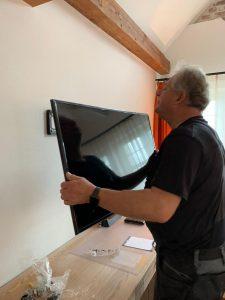 Hausmeister hängt TV auf im Golfpark Strelasund