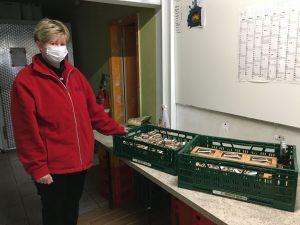 Eine Frau von der Grimmener Tafel steht vor den Spenden